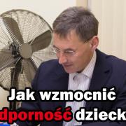 Doktor Paweł Grzywacz przy biurku wypisuje receptę