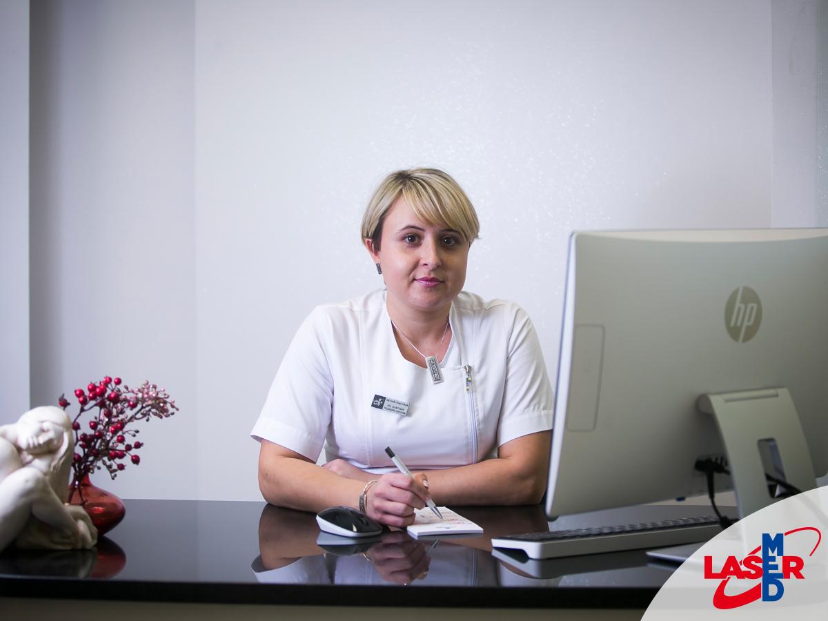 Amelia Langer-Łukasik specjalistka laseroterapii siedząca w gabinecie przed komputerem