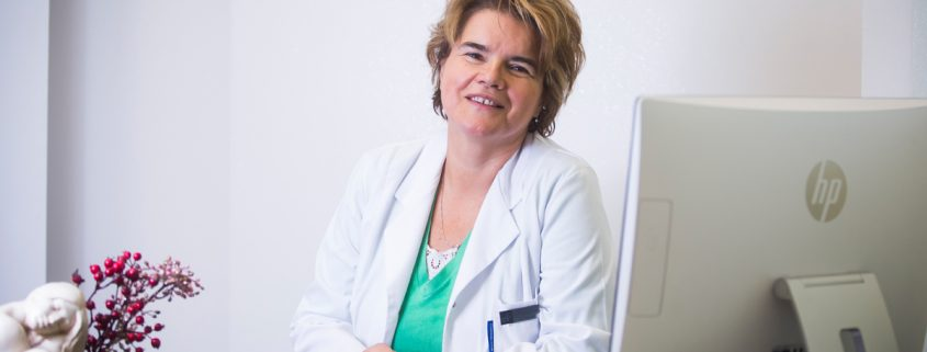 Lekarz dermatolog Katarzyna Dziubas-Stoch siedząca w gabinecie przed komputerem