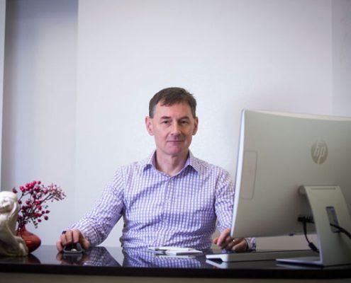 Doktor Paweł Grzywacz siedzący przy biurku w gabinecie kliniki LASERMED