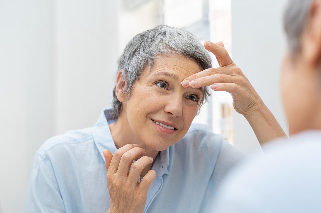 Jak pielęgnować dojrzałą skórę? - dojrzała kobieta patrząca na swoje zmarszczki